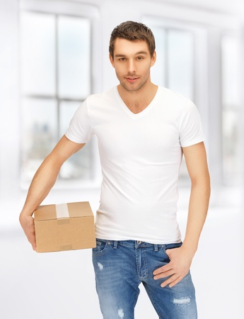 parsel: handsome man in white shirt with parsel Stock Photo