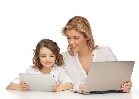 Niños ayudando: madre e hija con la computadora portátil y Tablet PC