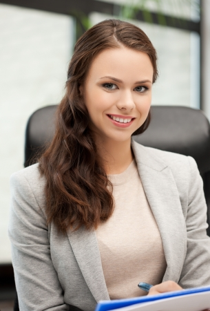 indoor picture of happy woman with documents writing something down Stock Photo - 18299789