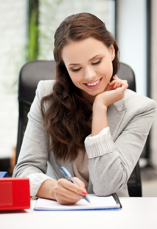 happy woman with documents writing something down Stock Photo - 18299814