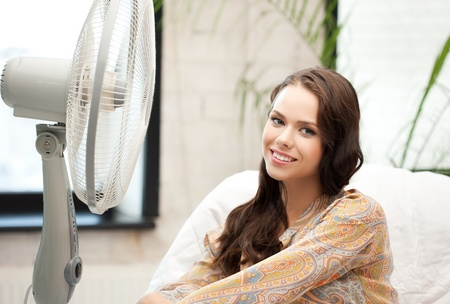 heat home: picture of happy and smiling woman sitting near ventilator