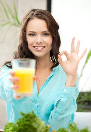 woman holding glass of orange juice and showing ok sign Stock Photo - 18299785