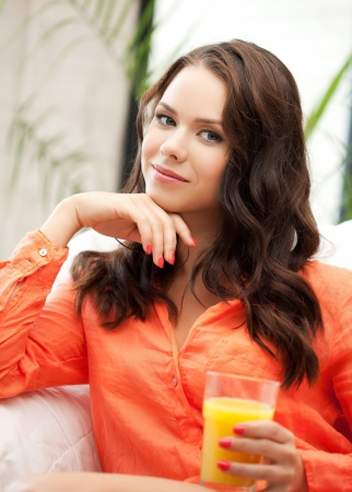 young woman holding glass of orange juice Stock Photo - 18299794