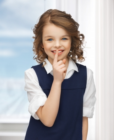 picture of beautiful pre-teen girl showing hush gesture photo