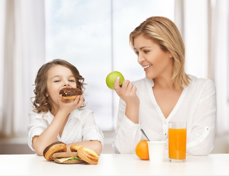 unhealthy snack: mother and daughter with healthy and unhealthy food