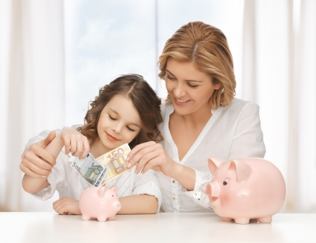pre adolescent child: mother and daughter with piggy banks and paper money