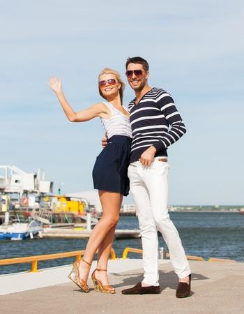 gente saludando: joven pareja feliz de pie y saludando en el puerto Foto de archivo