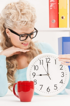 picture of attractive businesswoman with clock and red cup photo