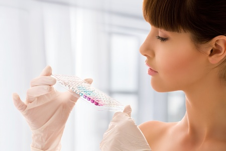 closeup of beautiful lab worker holding up reagents