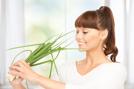spring onions: bright picture of beautiful housewife with spring onions in kitchen Stock Photo