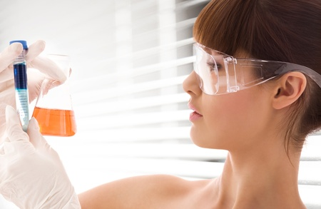 closeup of beautiful lab worker holding up test tubes photo