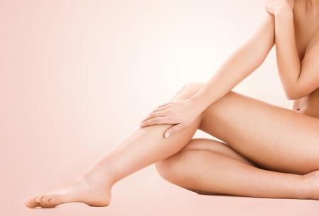 mujer desnuda sentada: imagen de saludables piernas de la mujer desnuda sobre fondo beige
