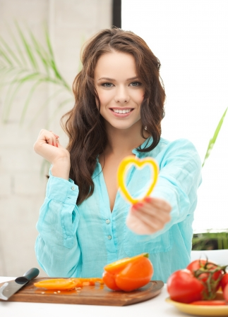 woman in the kitchen cutting vegetables and holding heart shape photo