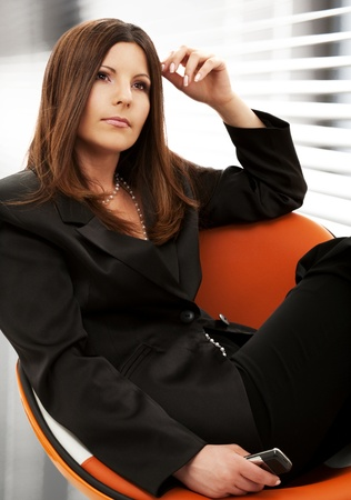 pensive businesswoman with cell phone in office photo