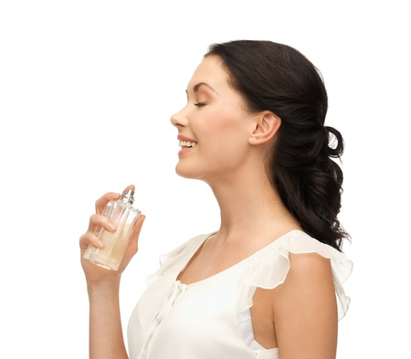 perfumer: picture of beautiful woman spraying pefrume on her neck