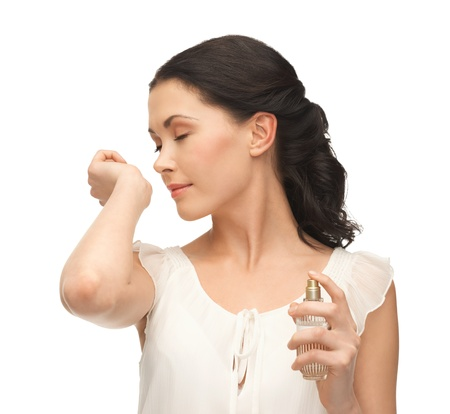 picture of beautiful woman smelling pefrume on her hand photo
