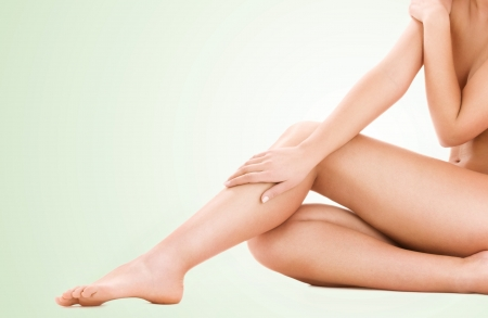 naked woman sitting: picture of healthy naked woman legs over green background Stock Photo