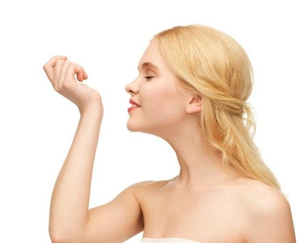 picture of young girl smelling pefrume on her hand photo