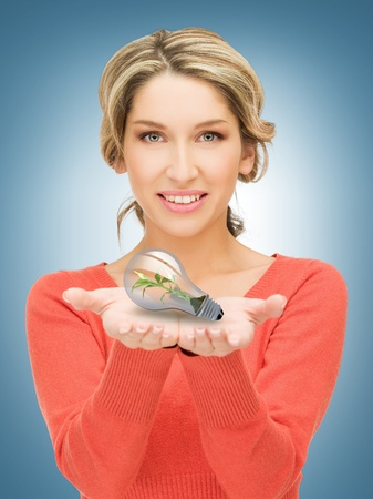woman showing green light bulb on her hands photo