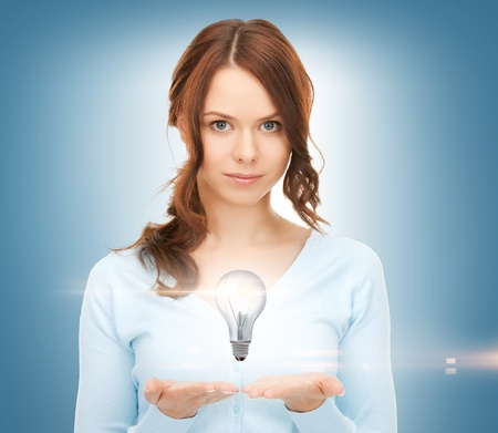 beautiful woman showing light bulb on her hands photo