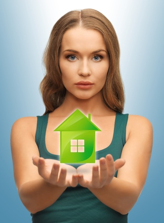 beautiful woman holding green house in her hands Stock Photo - 18530480