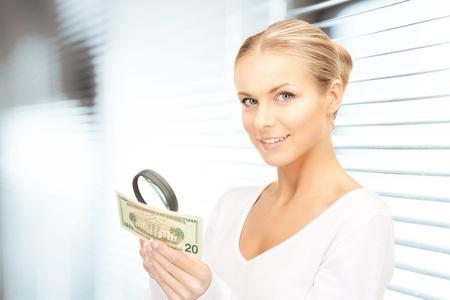 dinero falso: mujer encantadora con lupa y dinero Foto de archivo