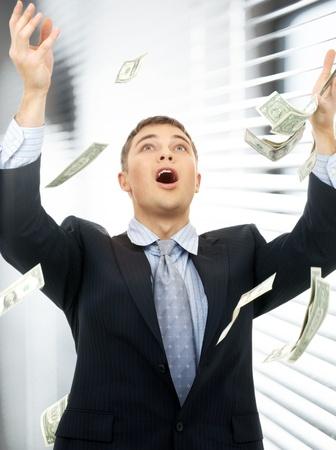happy successful businessman in money rain indoors photo