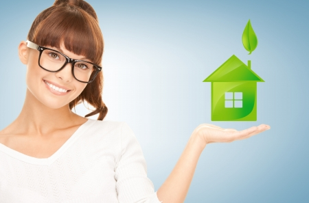 eco house: beautiful woman holding green house in her hands Stock Photo