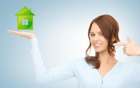 young woman pointing her finger at green eco house photo