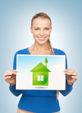 home protection: woman holding paper with illustration of green eco house Stock Photo