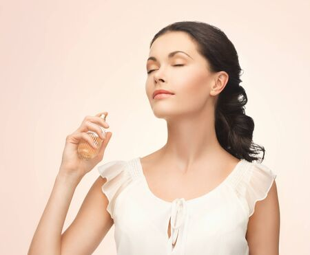 perfume woman: picture of beautiful woman spraying perfume on her neck Stock Photo