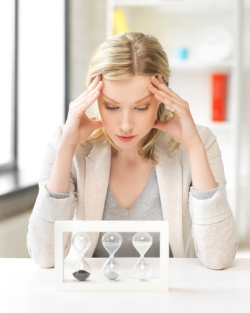 bored and tired woman behind the table with hourgalss Stock Photo - 18655041