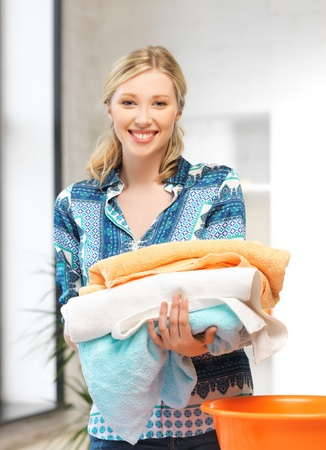 laundry pile: bright picture of lovely housewife with towels  Stock Photo