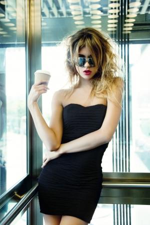 foto van meisje poseren in de lift met een kopje koffie Stockfoto