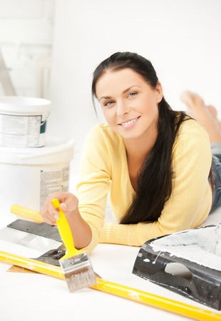 renovating: happy young woman with paintbrush and renovating tools