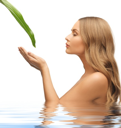 aging skin: picture of woman with green leaf in water Stock Photo