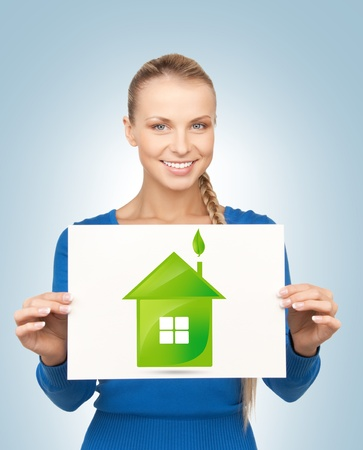 woman holding paper with illustration of green eco house illustration