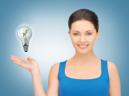 woman showing green light bulb on her hand photo