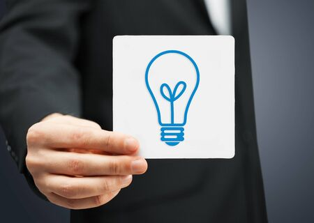 businessman showing sheet with sign of light bulb photo