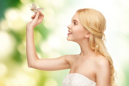 donna farfalla: immagine della bella donna con libellula in mano