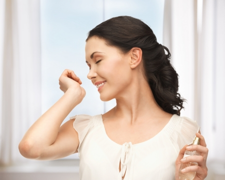 picture of beautiful woman smelling perfume on her hand photo