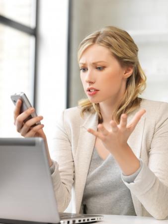 beeld van de verwarde vrouw met een mobiele telefoon Stockfoto