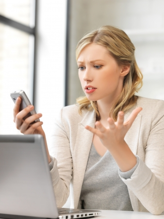 pissed: picture of confused woman with cell phone Stock Photo
