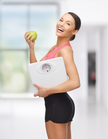 woman on scale: picture of beautiful sporty woman with scale and green apple Stock Photo