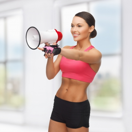 pointing device: sporty woman with megaphone pointing her finger at something Stock Photo