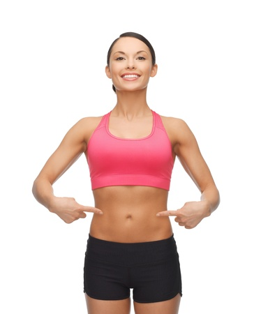 six pack: picture of beautiful sporty woman pointing at her six pack