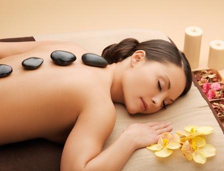 massaggio: immagine della donna in salone spa con pietre calde