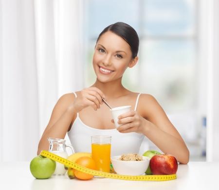 alimentacion balanceada: mujer joven con un desayuno saludable y cinta m�trica