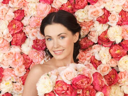portrait of beautiful woman with background full of roses photo