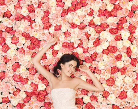 beautiful and young woman with background full of roses photo